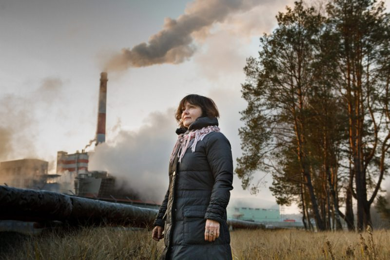 Human rights defender Alena Masliukova posing against the paper mill in Svietlahorsk. The factory has drawn much criticism from environmental activists