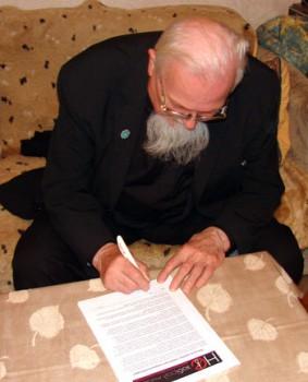 Аляксанд Надсан падпісвае петыцыю.