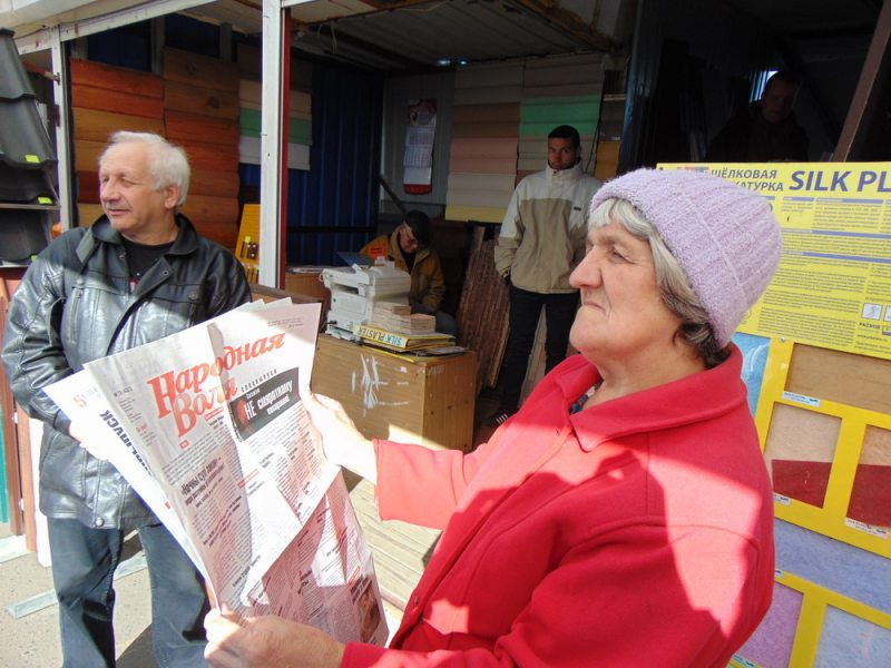 A woman reading the thematic issue of the Narodnaja Volia newspaper at a market in Rečyca. October 7, 2018