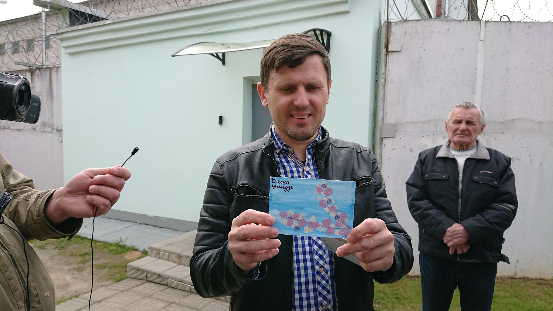 Аляксандр Буракоў паказвае паштоўку салідарнасці. Фота: Аляксей Колчын