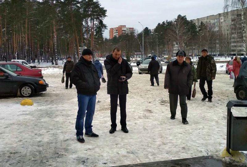 Невядомыя людзі сочаць за выбарчым пікетам Юрыя Ляшэнкі 8 лютага 2018 года.