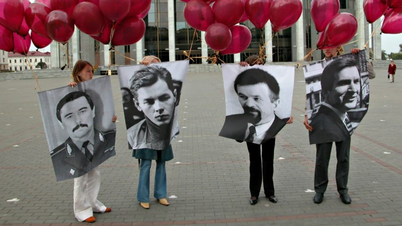 Protesters holding portraits of missing politicians at a street event in Minsk